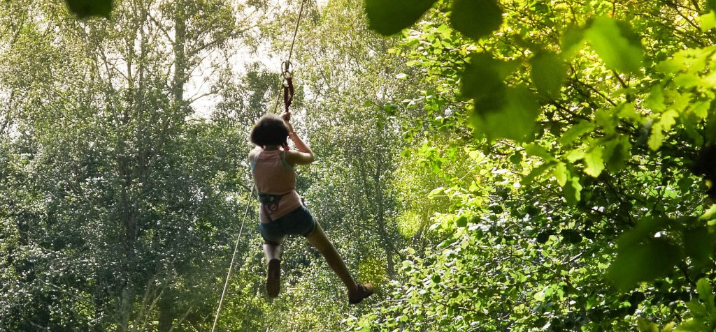 Chica de espalda volando en Tirolina en Selva Asturiana