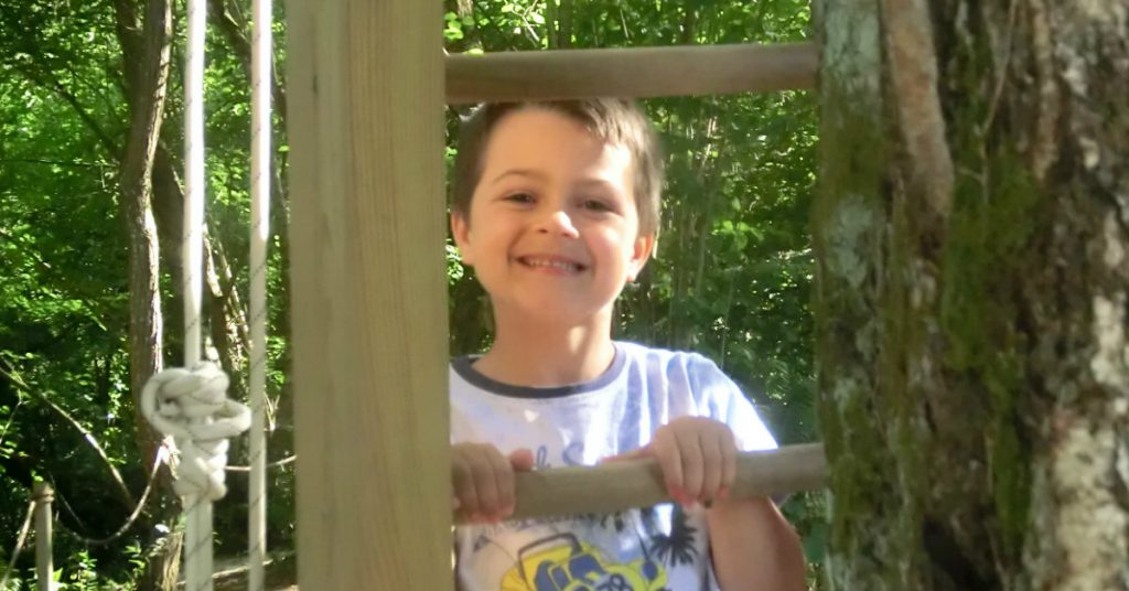 Niño sorriendo subiendo escalera en Selva Asturiana
