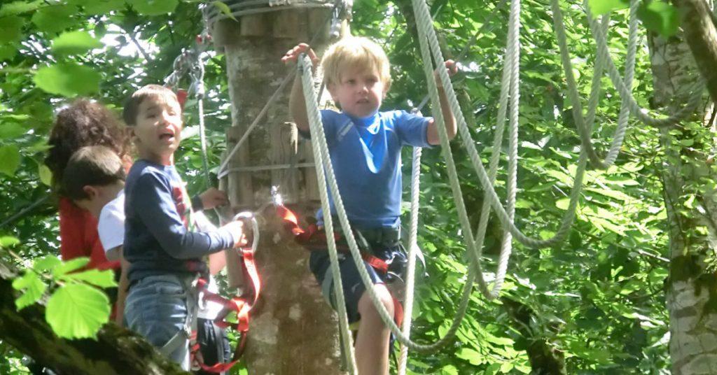 Niños cruzando un puente de cuerdas